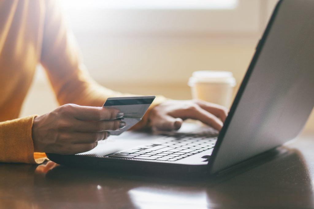 pessoa fazendo compra online com cartão de credito na mão